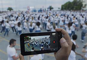 Pessoa filma multidão com smartphone